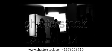 Shooting studio behind the scenes in silhouette images which film crew team working for filming movie or video with professional lighting and equipment such as camera, tripod, soft box, monitor #1376226710