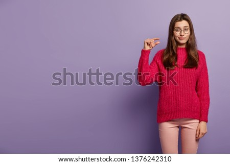 Unhappy Caucasian lady makes little small gesture, demonstrates something tiny, has unhappy expression, wears red jumper and trousers, isolated over purple background. People and size concept #1376242310
