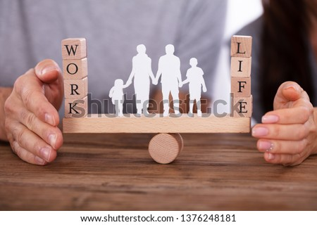 Couple Protecting Work And Life Balance With Family Figures Standing Between Them On Seesaw #1376248181