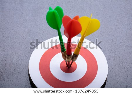 An Elevated View Of Colorful Darts On Target Against Gray Background #1376249855