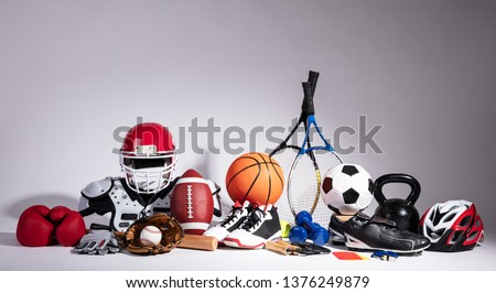 Variety Of Sport Balls And Equipment In Front Of Gray Surface #1376249879