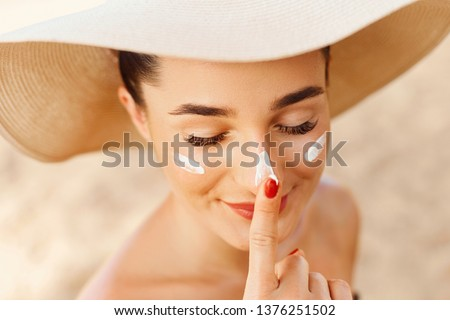 Beautiful Young woman with sun cream on face. Girl holding sunscreen bottle on the beach. Female in hat applying  moisturizing lotion on skin.Skin care. Sun protection. Suntan #1376251502