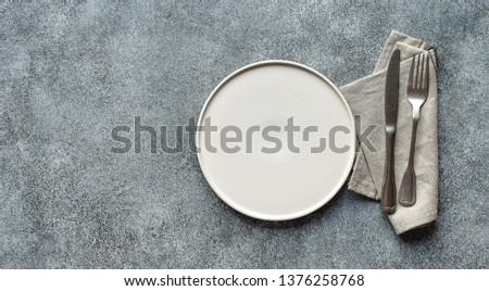 White craft plate, cutlery and napkin on white stone table. knife and fork on beige napkin. Top view, copy space. Table setting. background for menu, layout, recipe background, food flat lay #1376258768