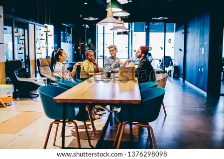 Positive multiracial crew of employees having brainstorming session cooperate  at modern interior office, positive male and female colleagues discussing creative solution for startup project #1376298098