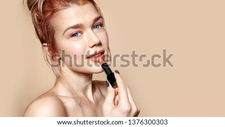 Portrait of gorgeous smiling woman holding rosy lipstick in hand. Model posing in studio and looking in camera gracefully. Beauty and cosmetics concept. Isolated on beige #1376300303