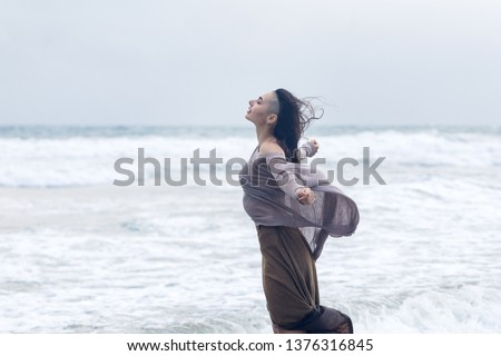 Lifestyle portrait of happy carefree young woman walking on the beach with space for text. #1376316845