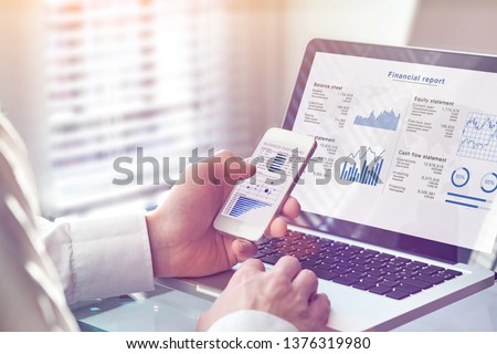 Accountant working on consolidated financial report of corporate operations, consultant auditing finance data (balance sheet, income statement) on screen with business charts, fintech, manager #1376319980