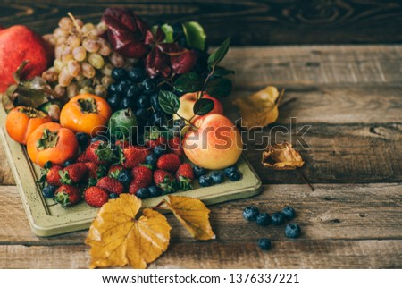Healthy fruits. Vintage tray filled with strawberries, blueberries apples, grapes, persimmon, pomegranate on rustic wooden background. Toned image. Selective focus. Copy space. #1376337221