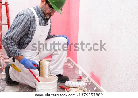 Caucasian house painter worker in white overalls, with helmet and goggles painting the pink wall with white paint using the brush. Construction industry. Work safety. #1376357882