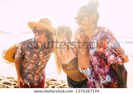 Group of cute friends people hug together and pose for a picture smiling - cheerful pretty girls and boys youthful concept for summer vacation at the beach - bright sun in backlight - friendship