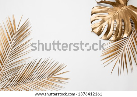 Golden painted tropical date palm and monstera leaves on plain white background isolated. Creative botanical layout border frame. Chic wedding invitation card mockup. Empty space, room for text.  #1376412161