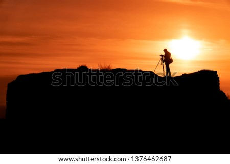 Silhouette of a photographer who shoots a sunset, on top of castle at sunset background. #1376462687