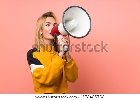 Young blonde woman over isolated pink background shouting through a megaphone #1376465756