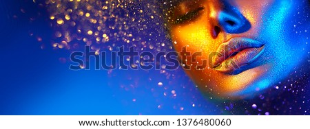 Fashion model woman skin face in bright sparkles, colorful neon lights, beautiful sexy girl lips, mouth. Trendy glowing gold skin make-up. Art design make up. Glitter metallic shine golden blue makeup #1376480060