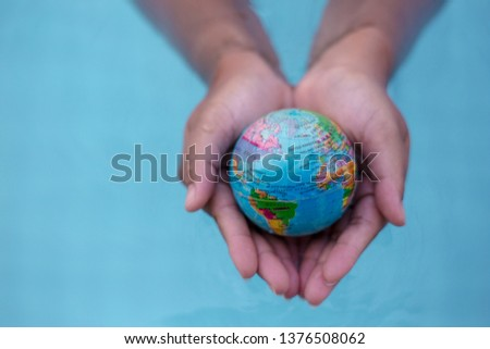 Close up imagery photo of hands holding world sphere with continents above water, perfect to represent ecology problem such as global warming with temperature rising around the globe. Save the planet