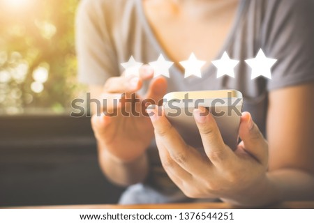 Customer service experience and business satisfaction survey. Woman hand using smart phone with icon five star symbol to increase rating of company concept Royalty-Free Stock Photo #1376544251