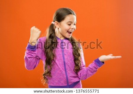 Product presentation. Kid happy face show something on open palm copy space. Girl demonstrate product. Advertisement and commercial concept. Promoting product for kids. Launching product for children. #1376555771