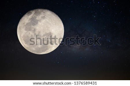 The big full moon at night with milky way group of stars background.