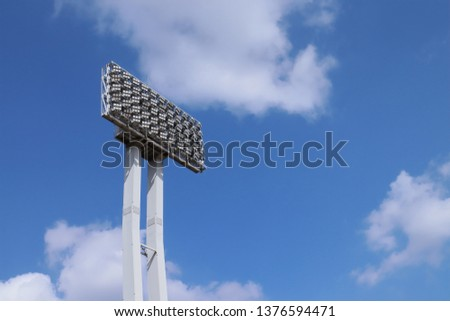 Stadium lights in a daytime with blue sky and white cloud #1376594471