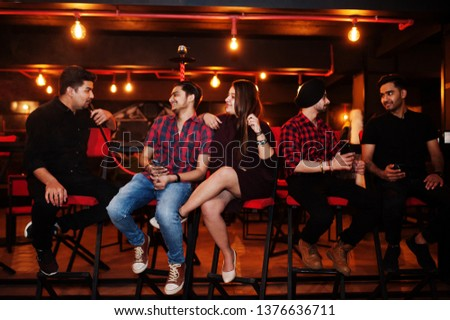 Group of indian friends sitting at lounge bar, smoke hookah and having rest. #1376636711