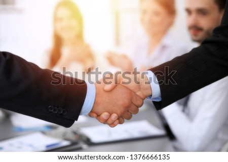 Business people shaking hands at meeting while theirs colleagues clapping and applauding. Group of unknown businessmen and women in modern white office. Success teamwork, partnership and handshake #1376666135