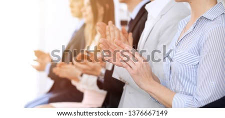 Business people clapping and applause at meeting or conference, close-up of hands. Group of unknown businessmen and women in modern white office. Success teamwork or corporate coaching concept #1376667149