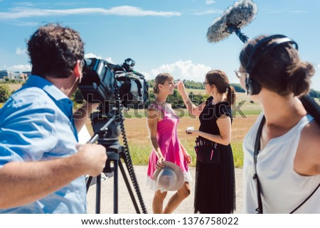 Video shoot with crew, make-up artist, and model on set