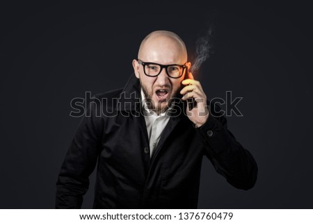 Male businessman with an evil face in a white shirt and dark cloak talks and shouts by telephone on a dark background. Concept stress, bad business, anger, too many phone calls. #1376760479