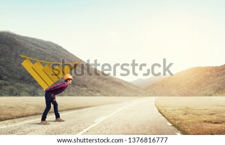 Young man builder carrying growing graph on his back #1376816777