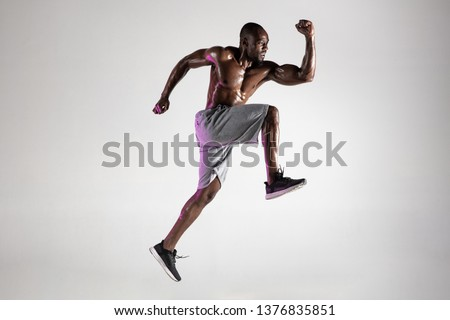 Run for adventures. Young african-american bodybuilder training over grey studio background. Muscular single male model jumping in sportwear. Concept of sport, bodybuilding, healthy lifestyle. #1376835851