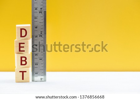 Measuring size of debt, public debt market measurement, financial concept : Cubes of debt and a ruler scale, depicts debt level debtor owes its creditor, debt is reduced by restructuring, refinancing #1376856668