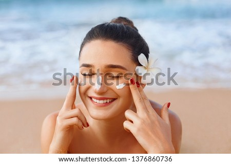 Beautiful woman applying cream sunscreen on a tanned face. Sunscreen. Skin and body care. The girl uses a sunscreen for her skin. Portrait of a female holding suntan lotion and moisturizing sunscreen. #1376860736