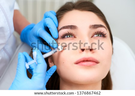 Doctor in medical gloves with syringe injects botulinum under eyes for rejuvenating wrinkle treatment. Filler injection for eye wrinkles smoothing. Plastic aesthetic facial surgery in beauty clinic #1376867462