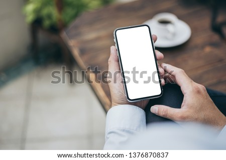 Mockup image of woman's hand holding using white mobile phone at outdoor with copy space,blank screen for text.concept for business,people communication,technology electronic device. modern life #1376870837