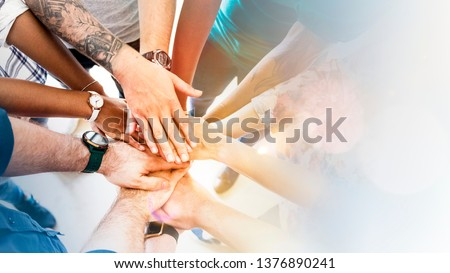 Diverse creative team stacking hands #1376890241