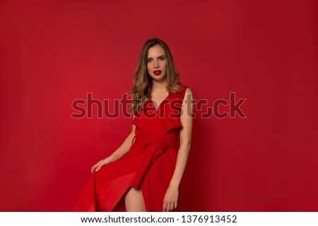 Elegant fashionable young woman wearing fantastic red dress posing over isolated red background  #1376913452