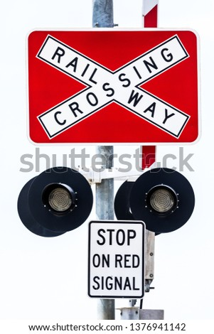 A close up vertical image of a railroad railway crossing sign post stop sign on a clean white background. See also same image with lights on. #1376941142