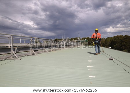Construction safety inspector wearing fall safety harness walking on the roof by clipping safety rope on fall arrest, fall restraint   horizontal safety line while inspecting fixed roof anchor points  Royalty-Free Stock Photo #1376962256