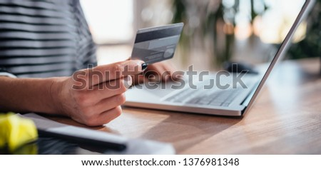 Woman using laptop and shopping online while holding credit card #1376981348
