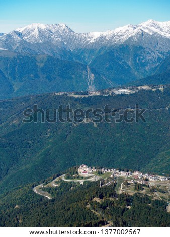Ski resort in the summer or autumn against the backdrop of snowy mountains on a sunny day. Krasnaya Polyana, Sochi, Russia #1377002567