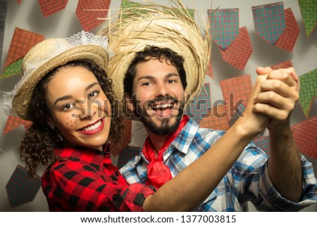 Festa Junina: party in Brazil in the month of june. Man and woman dressing checked pattern clothes. Man and woman dressing checked pattern clothes hold hands and dance together. #1377003815