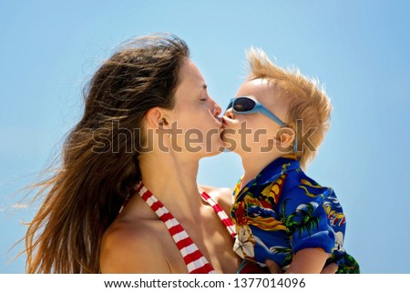 Happy beautiful fashion family, mom and children, dressed in hawaiian shirts, playing together on the beach, famiy joyful vacation #1377014096