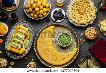Arabic Cuisine:Middle Eastern desserts. Delicious collection of Ramadan traditional desserts. Served with tasty nuts, dried fruits,honey syrup and oriental tea.Top view with close up. #1377022304