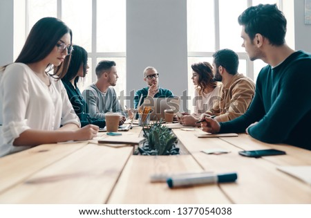 Staff meeting. Group of young modern people in smart casual wear discussing something while working in the creative office           #1377054038