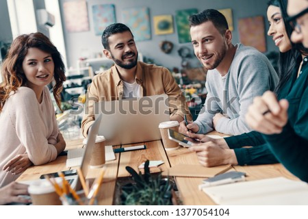 Collaboration. Group of young modern people in smart casual wear discussing something and smiling while working in the creative office   #1377054104