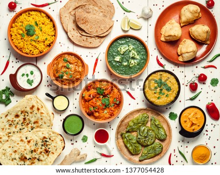 Indian cuisine dishes: tikka masala, dal, paneer, samosa, chapati, chutney, spices. Indian food on white wooden background. Assortment indian meal top view or flat lay. #1377054428