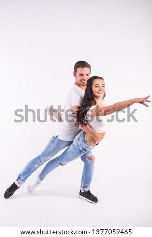 Young couple dancing social dance bachata, merengue, salsa, kizomba. Two elegance pose on white room. #1377059465