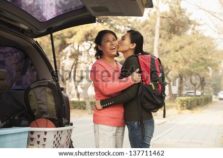 Mother and daughter embracing behind car on college campus #137711462