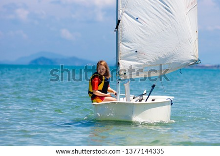 Child sailing. Kid learning to sail on sea yacht. Healthy water sport for school kids. Yachting class for young sailor. Children on boat. Family summer vacation on tropical island. Beach activity. #1377144335