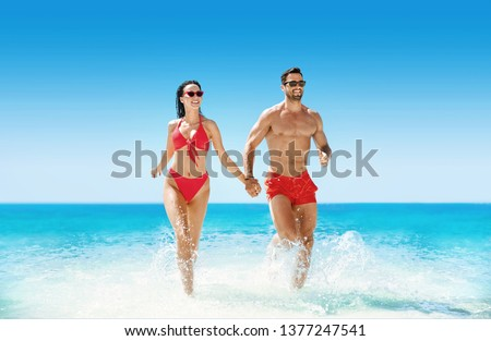 Young, attractive couple resting on a hot, tropical beach #1377247541
